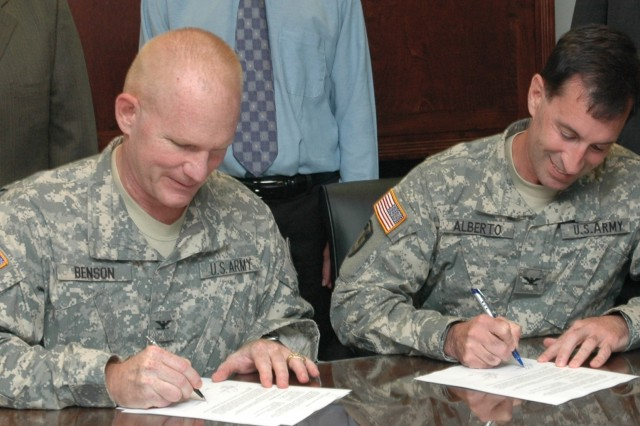Army Materiel Systems Analysis Activity Deputy Director Colonel Kirk C. Benson (left) and Tobyhanna Army Depot Commander Colonel Ron Alberto sign a Memorandum of Agreement between their two activities.