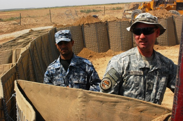 Staff Sgt. Kenneth Winters, Btry. A, 2-20th FA Regt. and Saad Nabareev, IP Special Response Team Three, reposition a Hesco barrier before it is filled with dirt, near the TCP at JSS Five Sept. 19.