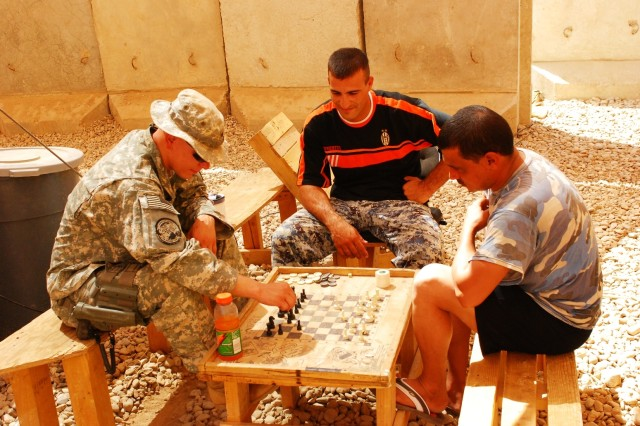 Sgt. Dallas Bartel, Btry. A, 2-20th FA Regt., plays chess against Haider Alawi IP, Special Response Team Three at JSS Five Sept. 19.