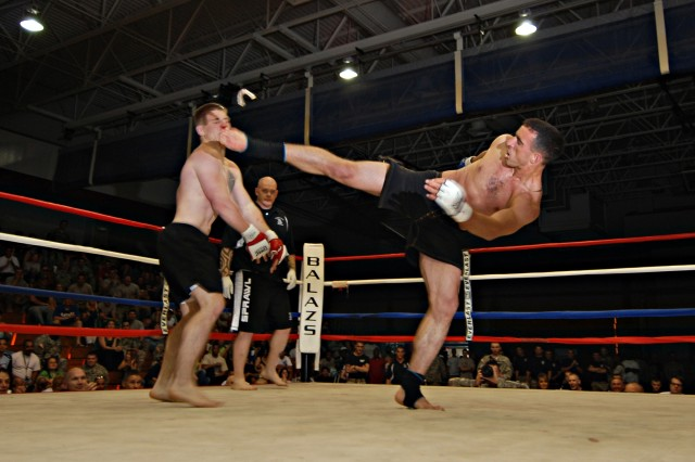 Fresno, Calif. native Pfc. Patrick Murphy (right) of 1st Battalion, 325th Airborne Infantry Regiment, delivers a vicious kick to the head of Pvt. Zach Rabenold, of 2nd Battalion, 505th Parachute Infantry Regiment in their bout during the final night of the modern army combatives tournament held as part of the 82nd Airborne Division's All American Week celebration at Fort Bragg May 21. Murphy went on to win his weight class.