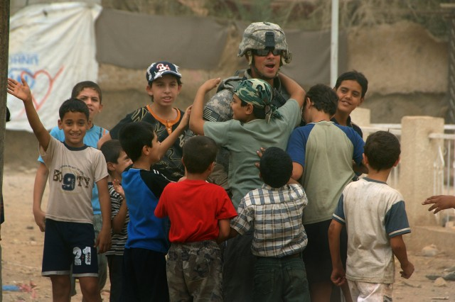 A Soldier from Charlie Company, 2nd Battalion, 30th Infantry Regiment, 4th Brigade Combat Team, 10th Mountain Division receives farewell hugs from a group of boys living in a Palestinian community in Baladiyat, eastern Baghdad, Sept. 14. His unit, along with Iraqi national police, were there handing out humanitarian aid bags to help foster good relations with the Palestinian community and the Iraqi security forces during Ramadan.