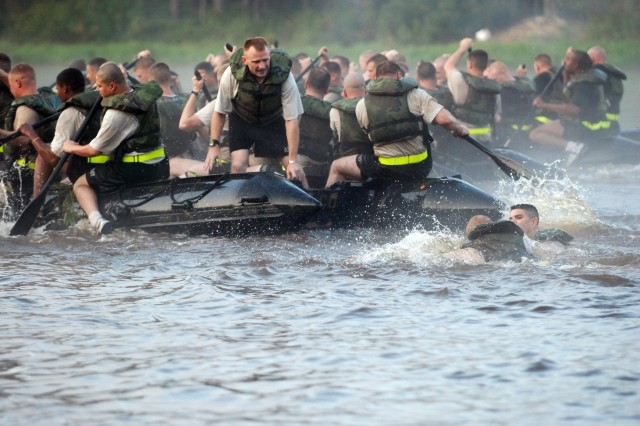 Two engineers from Company A, 2 Brigade Special Troops Battalion, 82nd Airborne Division, swim towards their boat after falling overboard during the Crossing of the Waal re-enactment race at McKellars Lake.