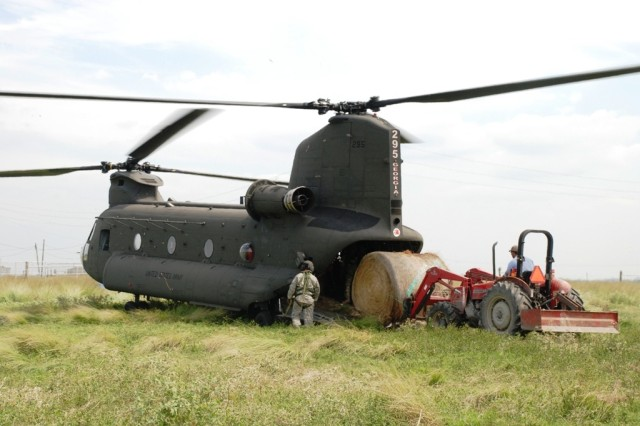 National Guardsmen help guide a rancher as he loads bundles of hay aboard a CH-47 Chinook helicopter to deliver to stranded livestock who have been trapped by the flooded salt-waters without food or fresh water since Hurricane Ike struck the Southwest coast of Louisiana.