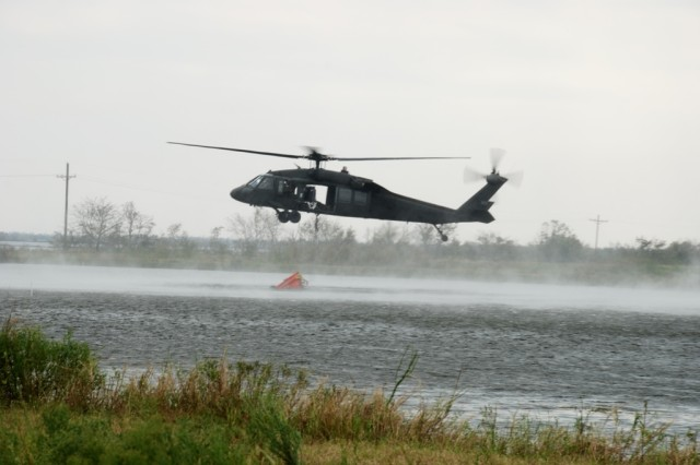 National Guardsmen of A Company, 1-185th Aviation Battalion from the Mississippi National Guard assist Louisiana Guardsmen in retrieving water from a  pond just south of Vinton, La.  They are using the water to fill water troughs along the inner coastal waterway for  cattle stranded without fresh water due to flooding from Hurricane Ike.