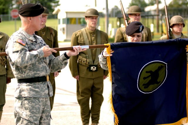 """Maj. Gen. Charles Gorton holds the 81st Regional Support Command """"Wildcat"""" colors as Command Sgt. Maj. Roxanne Castille carefully rolls the colors during a casing ceremony held on Sept. 21, 2008, in Birmingham, Ala. The 81st RRC will move to Fort Jackson, S.C., and be re-established as the 81st Regional Support Command."""