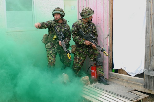A British Army Section commander with the 3 Company, 1st Battalion Welsh Guards shouts commands to the rest of his section under the concealment of green smoke as they search the buildings of the Mud Hut Village training facility in the Joint Multinational Readiness Center, Sept. 20. The JMRC is hosting the American, British, Canadian, Australian and New Zealand Armies' Program training event -- Cooperative Spirit 2008. The goal of the training event is interoperability - making sure the nations can not only talk electronically despite different communication systems but also work together tactically.