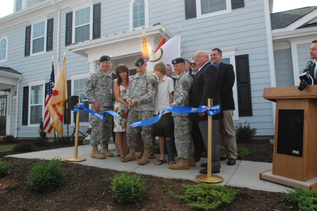 "Col. Jack Pritchard and his family cut a ribbon outside of a home in ""the Meadows,"" a Residential Communities Initiative housing development at Carlisle Barracks, Pa.  The ribbon cutting was part of a ceremony to celebrate the housing project, which includes the first new family housing built on Carlisle Barracks since the late 1960s."