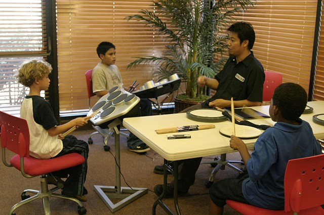 SCHOFIELD BARRACKS, Hawaii - Ted Tolentino, center, demonstrates a drum pattern to Rock School students. Rock School is a great way to introduce music to beginners and allow them to intimately experience their favorite rock songs.