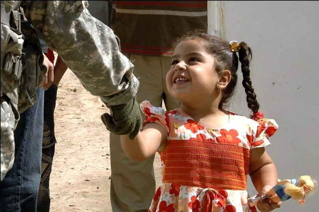 A young Iraqi girl shakes the hand of a Soldier at the Neighborhood Activities Center in the Gazaliyah district, Baghdad, Iraq, Sept. 21. The Soldier is assigned to the 2nd Brigade Combat Team, 101st Airborne Division.