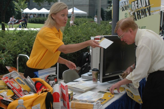 Patricia Powell, a representative of the Army Asymmetrical Warfare Office, the proponent for Ready Army, provides literature to a visitor at the Emergency Preparedness Fair Sept. 24 at the Pentagon.