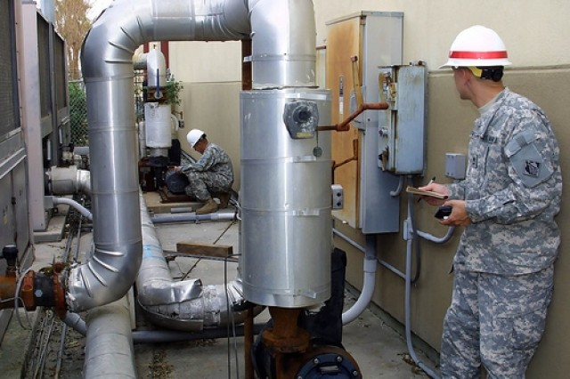 Sgt. 1st Class Thaddeus Pilewski (right) and Sgt. Leandro Rocha check the electrical requirements for an air conditioning unit at the Island Community Center Sep. 19 in Galveston, Texas. Teams of power experts from the U.S. Army Corps of Engineers' 249th Engineer Battalion (Prime Power), Fort Belvoir, Va., are conducting power assessments prior to installing temporary emergency power at critical public facilities in areas of Galveston affected by Hurricane Ike. The Corps assists the Federal Emergency Management Agency by coordinating and organizing public works and engineering-related support. (US Army Corps of Engineers photo by Brooks O. Hubbard IV)