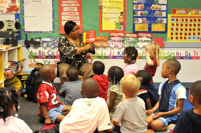 Joyce Matthews, lead pre-kindergarten teacher at the Fort McPherson Child Development Center, demonstrates to students how to call 