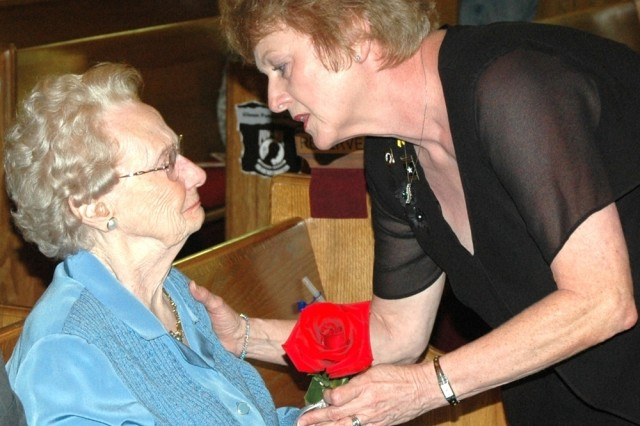 Donna L. Craven, right, director of religious education for the U.S. Army Garrison Chaplain's Office, presents a rose to Christine Jones Sept. 19 during the National POW-MIA recognition Day ceremony held at the Fort McPherson Post Chapel.The rose represents the life of each of the missing, and the families and friends of Americans who keep the faith, awaiting answers.  The stem of the rose was tied with a white ribbon, symbolic of the continued determination to account for the missing.Jones, 91, received definitive information in July about her son's death. Maj. Bobby M. Jones, an Air Force flight surgeon, had been missing in action since Nov. 28, 1972, when the jet he was in disappeared from radar near Danang in South Vietnam. Her daughter, Jo Anne Shirley, chairwoman of the board of directors of the National League of Families of American Prisoners and Missing in Southeast Asia and co-founder of the Georgia Committee for POW-MIAs Inc., was the event's guest speaker.