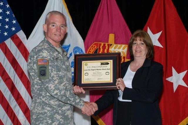 Maj. Gen. Scott G. West presents Mary Nelson with the Department of the Army Master Blackbelt Certificate.