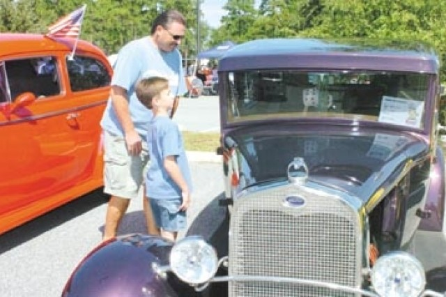 Willie Connor and son Cato check out the classic cars at the exhibit.