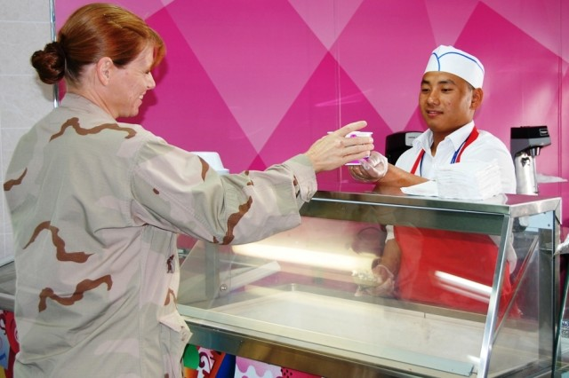 Nepal native, Shurresh Limbu, a waiter with Tamimi Global Co., serves dessert to U.S. Navy Lt. Julie Loftus, at Camp Arifjan, Kuwait's Zone 2 Dining Facility, Sunday, Sept. 28, 2008.  Loftus is a nurse assigned to Expeditionary Medical Facility - Kuwait. EMF-K staffs the 44-bed U.S. Military Hospital Kuwait, and includes more than 300 Navy medical personnel from 30 different health care facilities, providing care to coalition forces in Kuwait.