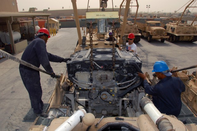 A team of ITT Corp. mechanics pull the engine from an M88 Armored Recovery Vehicle at the 2nd Battalion, 401st Army Field Support Brigade maintenance area at Camp Arifjan, Kuwait, Sept. 25.  Removing the engine allows the mechanics access the brakes, which are due a service.  Pictured are (L-R) Michael Houser, New York, N.Y., Nicky Calderone, New York, N.Y., Tony Hernandez, Kaufman, Texas and Charles Walker, Dacula, Ga.