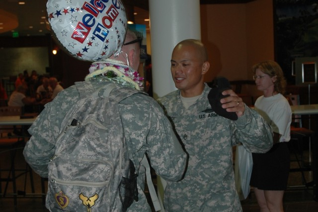 HONOLULU - Staff Sgt. Erwin Saddi, right, welcomes Sgt. Nathan Rolens home at Honolulu International Airport, Sept. 17, 2008. Saddi and Rolens were both injured July 8, 2008, when an IED struck their Stryker vehicle.
