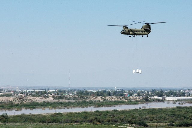 """A CH-47F Chinook helicopter from the Company B """"Black Cats,"""" 2nd Battalion, 227th Aviation Regiment, 1st Air Cavalry Brigade, 1st Cavalry Division, sling loads three oversized sandbags on their way to a levee in Presidio, Texas, near the Rio Grande River. The Black Cats are currently assisting the town by dropping the sandbags near a portion of the river that is threatening to overflow."""