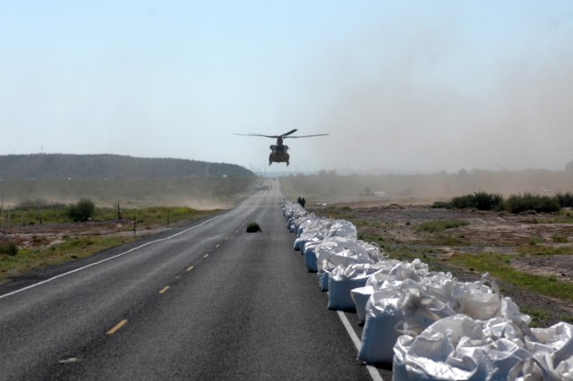 """A CH-47F Chinook helicopter from the Company B """"Black Cats,"""" 2nd Battalion, 227th Aviation Regiment, 1st Air Cavalry Brigade, 1st Cavalry Division, approaches a road in Presidio, Texas, to pick up sand bags Sept. 22. The Black Cats are currently supporting flood relief efforts for the town of Presidio by dropping the oversized sandbags on a levee to keep the high waters of the Rio Grande River from flooding the city."""
