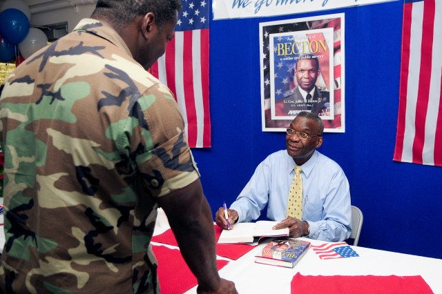 "Retired Lt. Gen. Julius Becton Jr. autographs his new book ""Autobiography of Becton -- a Soldier and Public Servant"" for Air Force Lt. Col. James Tarver at the Pentagon last week."