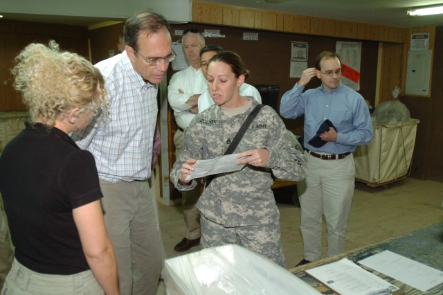 Staff Sgt Stephanie Zolnak, technical inspector for postal services on Joint Base Balad, explains the process absentee ballots go through after they are delivered to Joint Base Balad post offices to the Hon. Delbert Hosemann, the Secretary of State for Mississippi.  Hosemann visited the 3d ESC and Joint Base Balad to promote voting participation by Servicemembers and learn about overseas voting processes.