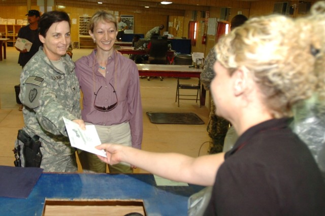 Debra Bowen, California's Secretary of State joins Col. Cheri Provancha, 3d Sustainment Command (Expeditionary) support operations officer in charge, as she turns in her official California absentee ballot to Stacy Fayas, Joint Base Balad East Side Post Office acting supervisor and administration specialist.  Provancha, whose section is responsible for distribution and tracking of all absentee ballots in theater, was part of Tuesday's tour of Balad's mail facilities with Secretaries of State from across the U.S.