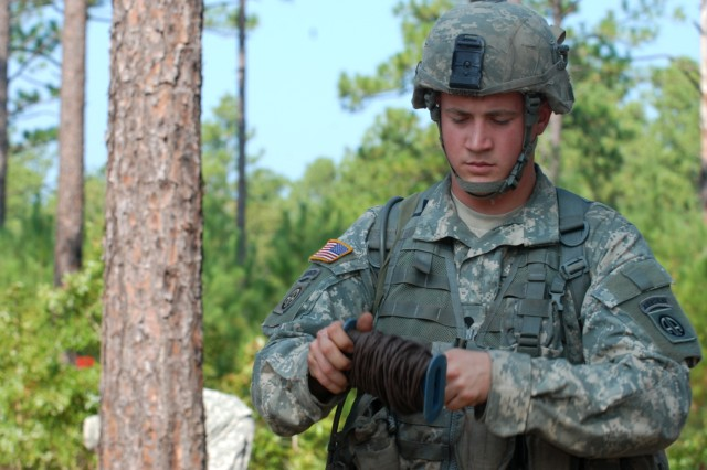 Spc. John Todoroff unrolls some firing wire for a claymore mine during a practice for the Expert Infantryman Badge on September 29. Setting up and retrieving a claymore mine is just one of the 32 test that Todoroff will have to perform come test day.  (U.S. Army photo by Sgt. Susan Wilt, 2nd BCT, 82nd Abn. Div. PAO)