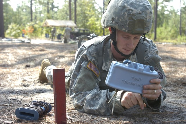 Sgt. Ty Lipe, a St. Louis native, sets up a claymore mine during a practice run for the Expert Infantryman Badge on September 29. Come test day Lipe will have to perform 32 tasks to receive his badge.  (U.S. Army photo by Sgt. Susan Wilt
