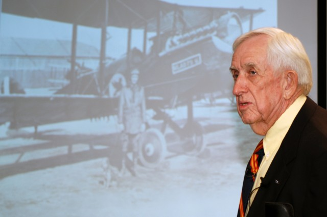 John Paul Jones, a local aviation artist and historian, gives a lecture on El Paso's aviation history while he stands in front of a photograph of a pilot and his plane on the Fort Bliss Flying Field.