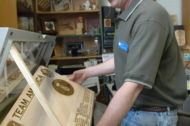 Joe Foley, engraver for the Arts and Crafts Center in Heidelberg, Germany, uses the laser engraving machine to complete a wooden plaque. Foley can engrave wood, glass, metal and other materials.