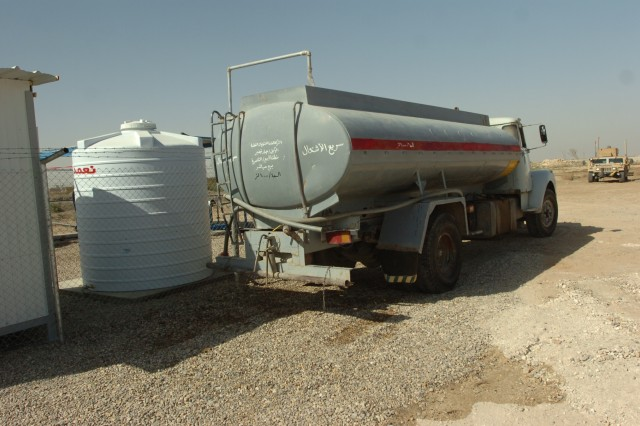 An overhead water delivery system fills a truck with water Sep. 30 at Abdul Razaq, Iraq. The Abdul Razaq water purification unit can process 700 gallons of fresh water an hour.