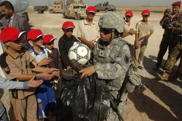 Spc. Diana Rubio, a member of the 7th Sustainment Brigade, hands out shoes and soccer balls Sep. 30 at Abdul Razaq, Iraq. The 7th SB participated in a ribbon-cutting ceremony for a water purification unit with Iraqi Army and Dhi Qar province officials.