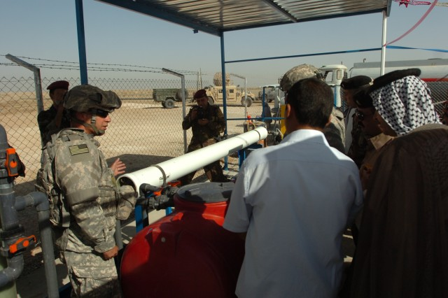 Chief warrant officer Chris Gauthreaux, a member of the 7th Sustainment Brigade, explains how the reverse osmosis water purification unit will work during a ribbon-cutting ceremony Sept. 30 at Abdul Razaq, Iraq. Gauthreaux, a native of New Orleans, works for the 7th SB's civil-military operations office.
