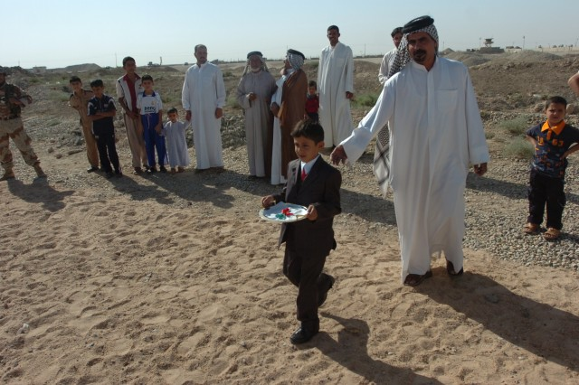 A young Iraqi boy carries scissors on a tray Sept. 30 at Abdul Razaq, Iraq. The scissors were used in the Abdul Razaq Water Purification Unit ribbon-cutting ceremony by members of the 7th Sustainment Brigade, Iraqi Army and local Iraqi leaders.