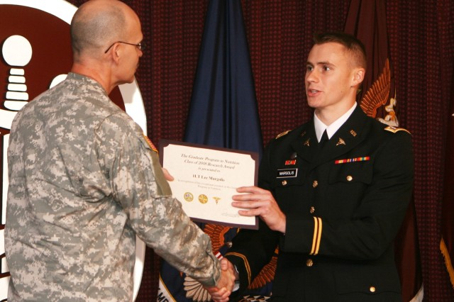 First Lt. Lee Margolis receives the Research Award from Col. George Dilly, the Army's chief dietitian, during graduation ceremonies Sept. 26 at the Cpl. Marvin R. Wood Auditorium at Fort Sam Houston. Margolis was one of 10 graduates in the first class in the Army's Graduate Program in Nutrition.