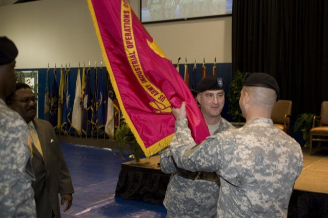 Incoming commander of Anniston Defense Munitions Center, Lt. Col. Duncan MacMullen (right), receives the ADMC colors from Blue Grass Army Depot Commander Col. Joseph Tirone here Sept. 25.