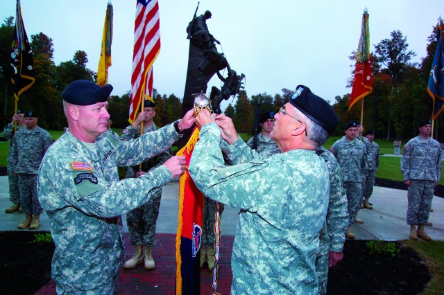Army Chief of Staff Gen. George W. Casey Jr., right; and Col. David B. Haight, 3rd Brigade Combat Team commander, place a combat action streamer on the brigade's colors Monday at Fort Drum's Memorial Park.