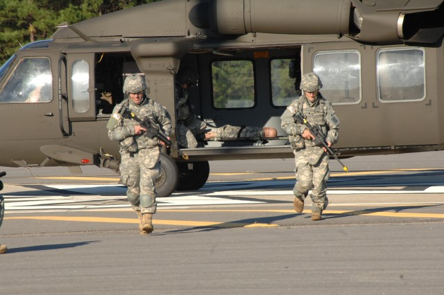 "The U.S. Army Training and Doctrine Command's Sgt. 1st Class Brian Eisch and Spc. Daniel Horner move away from aircraft after performing a medical evacuation.  The two were competing in the 2008 Department of the Army Noncommissioned Officer and Soldier of the Year ""Best Warrior"" Competition held Sept. 28-Oct.3 at Fort Lee, Va. (Photo by T. Anthony Bell)"
