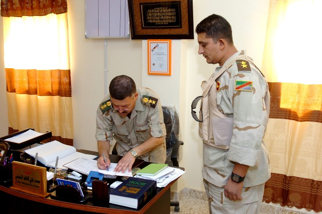 Col. Muhammad, commander of the General Truck Regiment at Camp Taji, Iraq, signs a work order, as part of his duties of coordinating and organizing functions in the regiment.