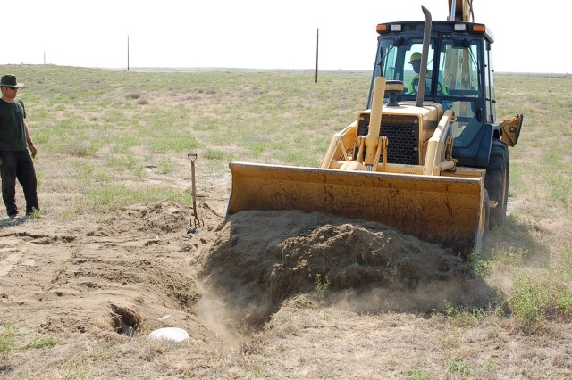 """Backhoe buries an Aca,!A""""owl condoAca,!A? site at the Umatilla Chemical Depot. Volunteers and staff finish covering the artificial burrow by hand."""