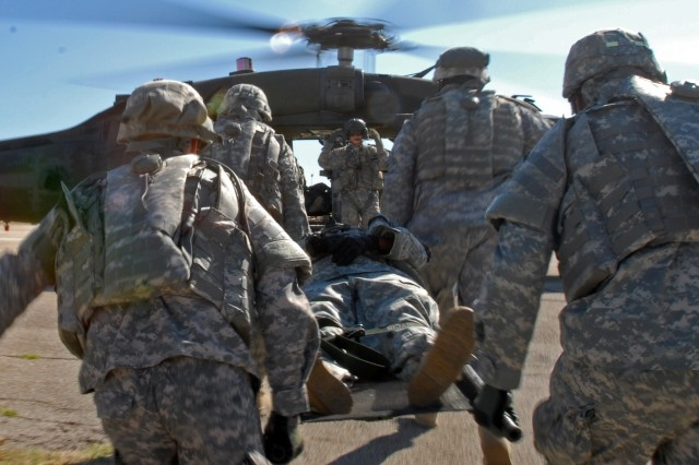 Soldiers from the 154th Transportation Company, 180th Transportation Battalion, 15th Sustainment Brigade, 13th Sustainment Command (Expeditionary), carry a simulated casualty to a medical evacuation helicopter during medevac training Oct. 2. The training is in preparation for the company's upcoming deployment.