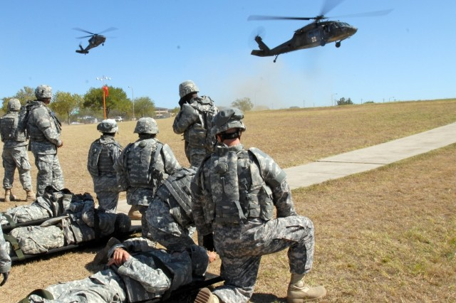 Soldiers from the 154th Transportation Company, 180th Transportation Battalion, 15th Sustainment Brigade, 13th Sustainment Command (Expeditionary), wait to load simulated patients on to the landing medical evacuation helicopters during medevac training Oct. 2.