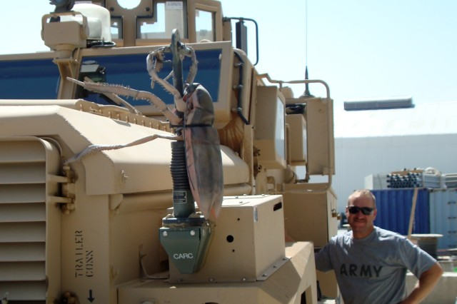 "Sgt. 1st Class Daniel Nastase, 1st Kandak, 3rd Brigade, 203rd Corps Embedded Training Team, poses beside his ""Cougar"" Mine Resistant Ambush Protected Vehicle, Sept. 27, 2008, in the Ghazni Province of Afghanistan.  Nastase is a combat advisor who, along with the rest of his team, mentors members of the Afghan military and police.  Editor's notes:    1)  A ""kandak"" is a battalion in the Afghan National Army.    2)  Sadly, the ""CARC""roach decorating Nastase's MRAP was stolen the day after this photo was taken."
