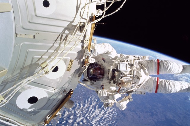 Astronaut  Col. Jeffrey N. Williams (Ret.), mission specialist, appears suspended over Earth in this 70mm photograph documenting part of the 6-hour, 44-minute space walk that he shared with James S. Voss in May 2000.  Williams and Voss also secured a U.S.-built crane that was installed on the station; replaced a faulty antenna for one of the station's communications systems; and installed several handrails and a camera cable on the station's exterior.