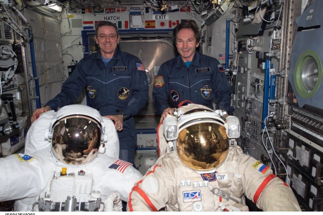 Astronaut Col. William S.  McArthur (left), Expedition 12 commander and NASA space station science officer, and cosmonaut Valery I. Tokarev, flight engineer representing Russia's Federal Space Agency, pose with a U.S. Extravehicular Mobility Unit spacesuit (left) and Russian Orlan spacesuit in the Destiny laboratory of the International Space Station, March 5, 2006.  McArthur, a retired Army colonel, has traveled into space four times.