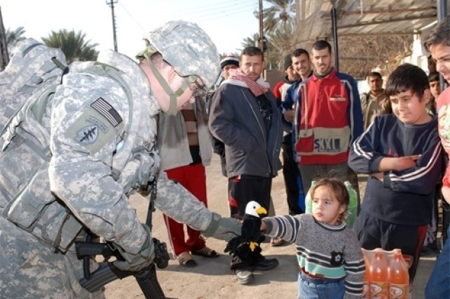 Maj. Brian Horine, civil affairs officer with the 3rd BCT, 4th Inf. Div., gives a stuffed animal to a little girl Jan. 14 during a convoy stop in Albu Hayat, Iraq. Horine carries stuffed animals and other treats for children with him when leaving Camp Taji to hand out. The Army's new field manual, FM 3-07, provides extensive doctrine on stability operations.