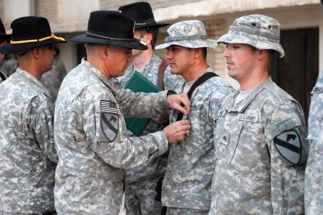 """Colonel Philip Battaglia awards Sgt. Javier Reyes and Sgt. Nicolas King with an Army Commendation Medal with """"V"""" device for valor at the Combat Action Awards Ceremony on COB Adder Sept. 19."""