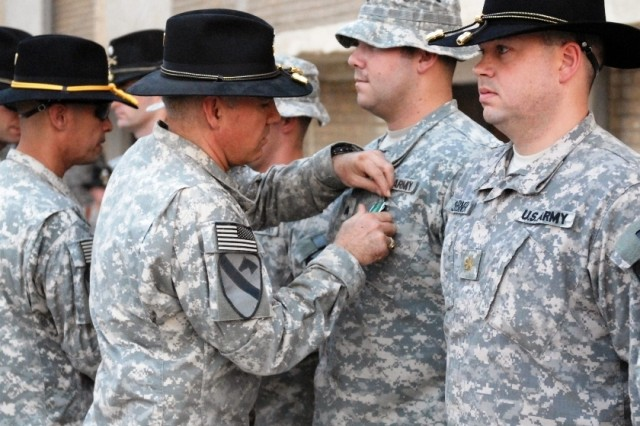"""Colonel Philip Battaglia, 4th BCT, 1st Cav. Div. commander, awards Sgt. Steven Robinson with an Army Commendation Medal with """"V"""" device indicating valor at the Combat Action Awards Ceremony on COB Adder Sept.19."""