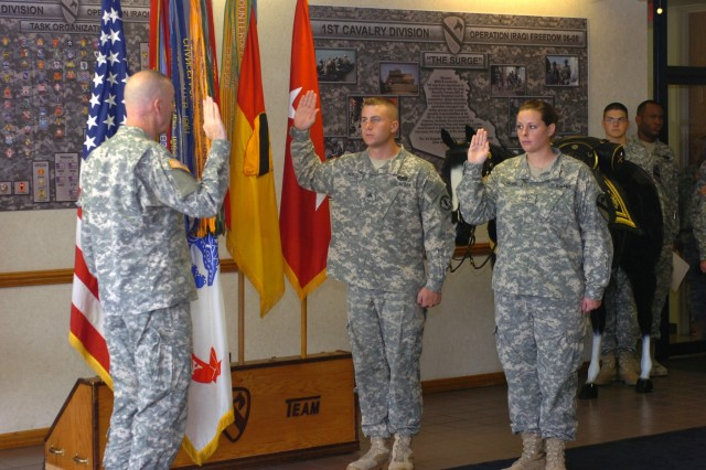 Maj. Gen. Daniel P. Bolger, commanding general, 1st Calvary Division, takes part in reenlisting two Soldiers at Fort Hood, Texas Sept. 22. Winfield, Kan. native, Sgt. Nathan Hayes (center), a military policeman, 64th Military Police Company, 720th MP Battalion, 89th MP Brigade, and San Antonio native, Pfc. Ryann Gilmore, a nuclear, biological and chemical specialist from Company B, Division Special Troops Battalion, raise their right hand as part of the ceremony.